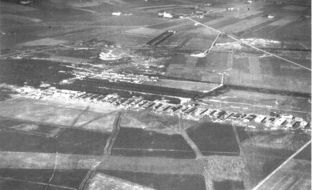 Foto: 1946 Romlejr I. med over 100 træbarakker, øst for Ringkøbingvej. Øverst ses Rom Kirke.